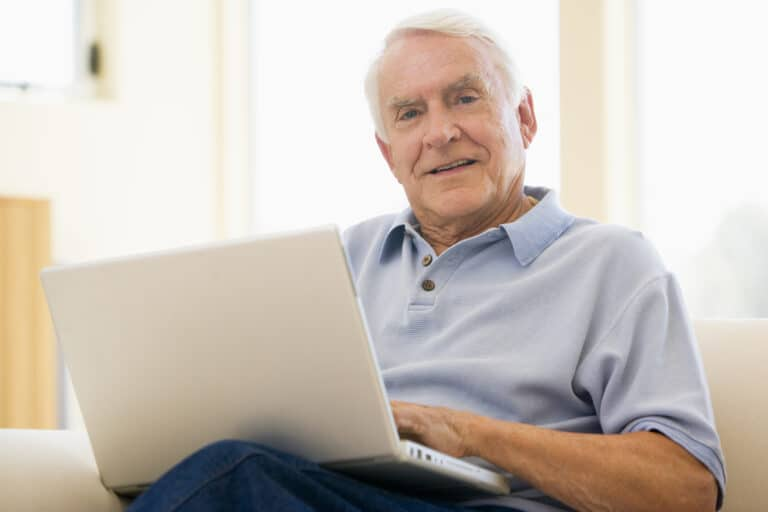 Senior man sitting on couch with laptop, smiling