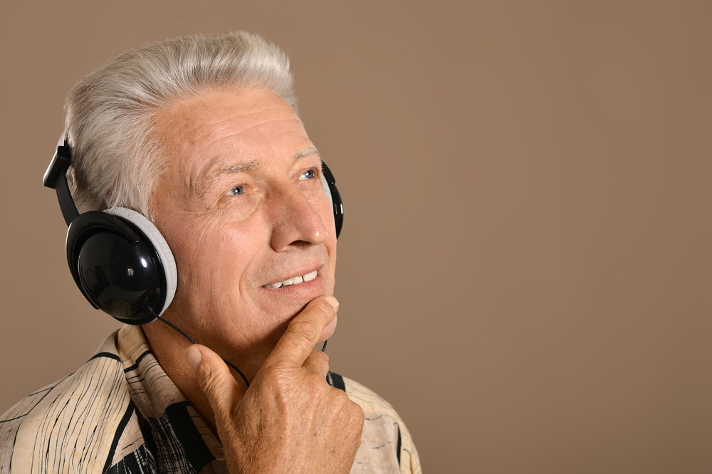 Senior man wearing headphones looking thoughtful