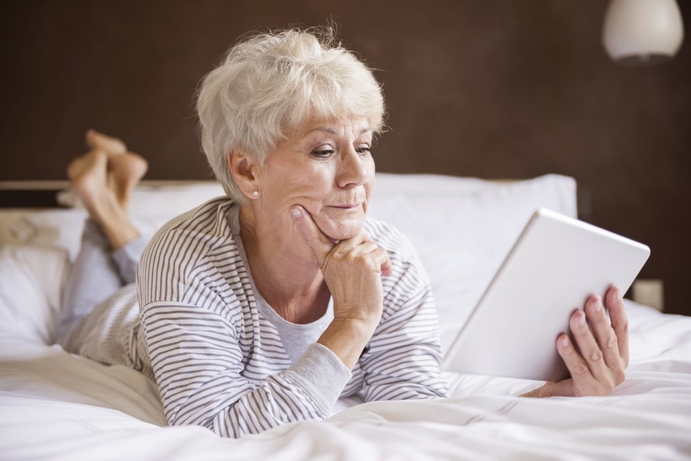 Senior woman looking thoughtfully at tablet in bed