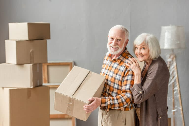 Smiling senior couple packing cardboard boxes