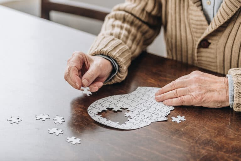 Close-up of senior man completing puzzle shaped like human head