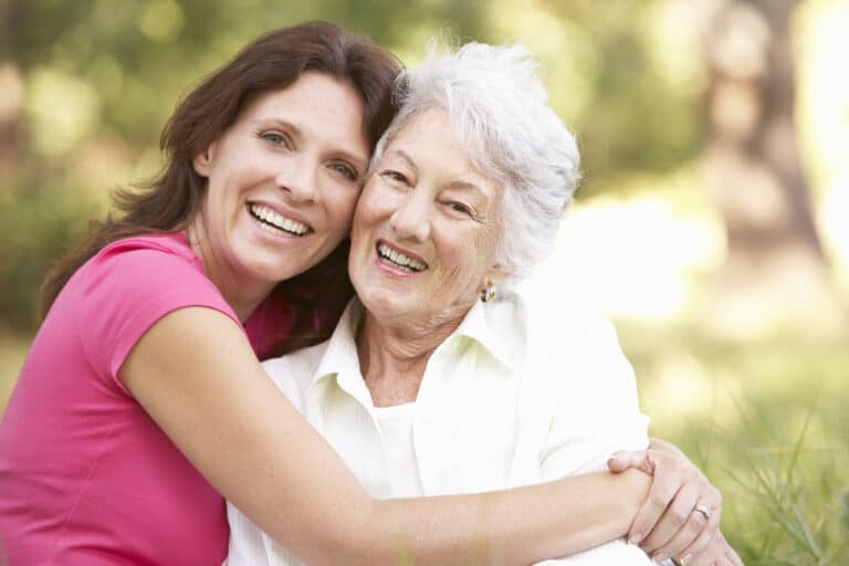 Senior woman and younger woman smiling and hugging outside