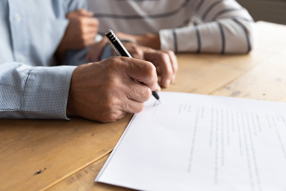Close-up of man signing paper, woman holding his arm comfortingly