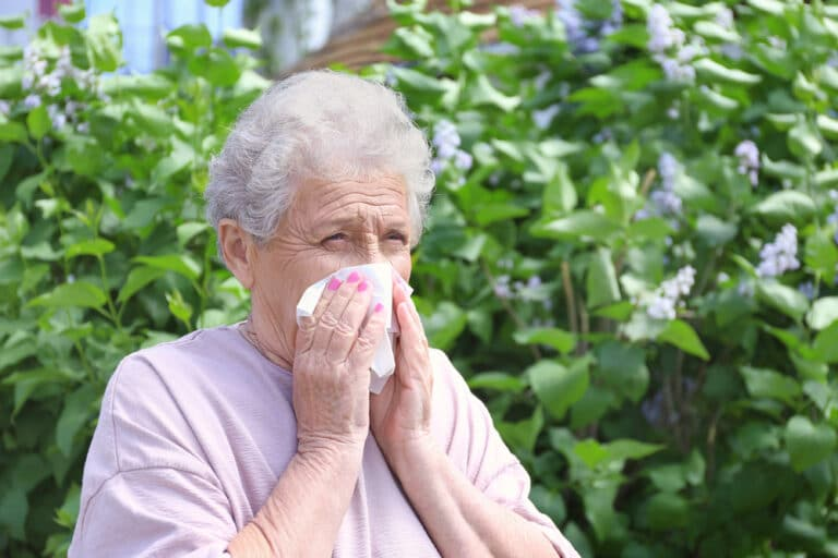 Senior woman blowing nose outside