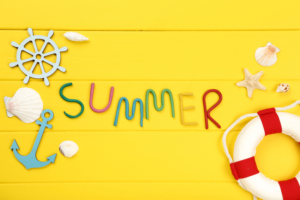 Summer spelled in clay letters, yellow background, wooden anchor and lifesaver