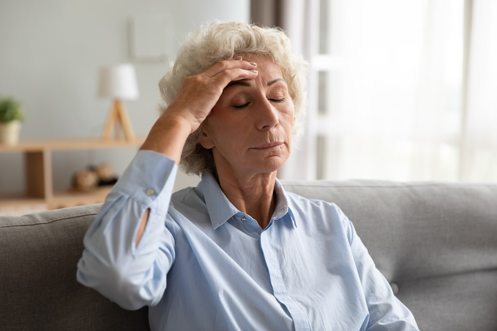 Senior woman on couch, holding hand to forehead, looking dizzy and distressed